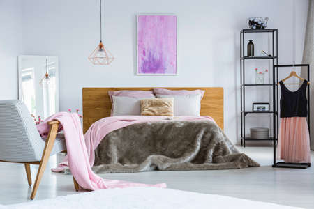 Pink and purple painting hanging above a double bed with wooden bedhead and decorative pillows in shabby bedroom interior