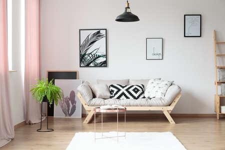 Hoofdkussens op beige bank tegen muur met affiches in eenvoudige woonkamer met koperlijst en varen