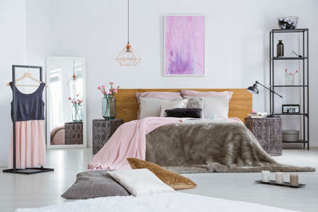 Decorative cushions lying in front of a double bed with fur duvet and metal nightstands in bright female room