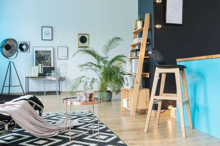 Geräumige Relax-Raum mit Barhocker auf Kücheninsel und Holzregal an der schwarzen Wand Standard-Bild - 86147768