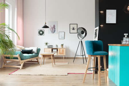따뜻한 방에 부엌 영역에서 파란색 바지 베개와 테이블 카펫에 터키석 settee 스톡 콘텐츠 - 86147773