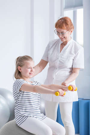 Active girl sitting on the ball and practicing with dumbbells while physiotherapist supports her