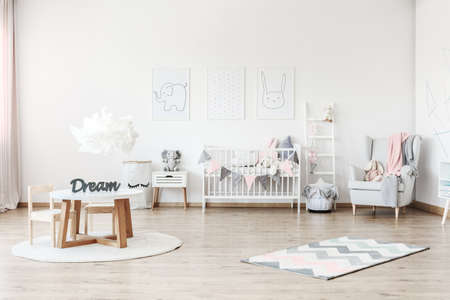 Pink blanket on grey armchair in pastel kids room with small table and plush toy on white cabinet Stockfoto