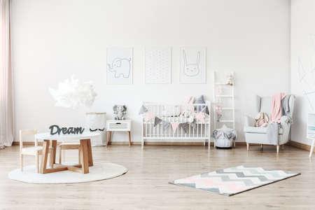 Roze deken op grijze leunstoel in de ruimte van het pastelkleurjonge geitje met kleine lijst en pluchestuk speelgoed op wit kabinet Stockfoto