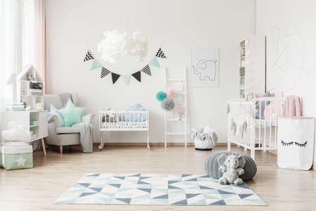 Grey pouf and plush toy on geometric carpet in spacious kids room with banner and paper bag for toys