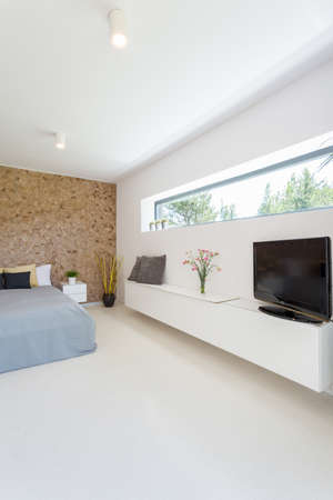 Bright spacious master bedroom with double bed and TV set