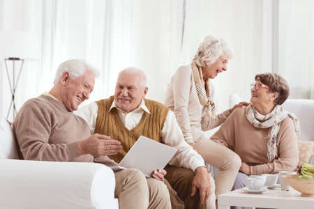 Senior friends are laughing and talking together while using laptop Stock Photo