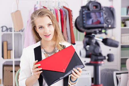 Young blonde vlogger holding a red and black bag and talking about fashion