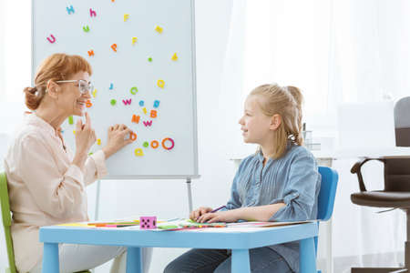 Speech therapist practicing correct mouth position with girl while sitting at blue table during speech therapy