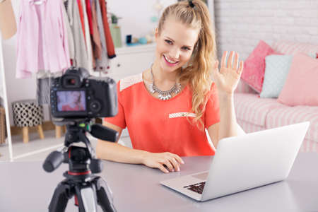 Pretty blonde vlogger sitting by the desk with laptop and recording her journal