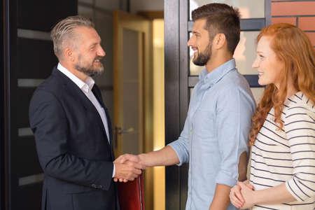 Glimlachende zakenman in zwarte kostuum welkom hetende studenten bereid om flat te huren