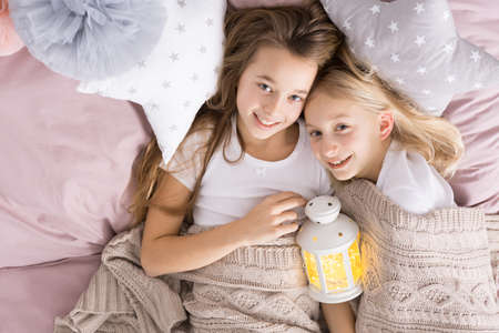 Happy little sisters lying together in bed