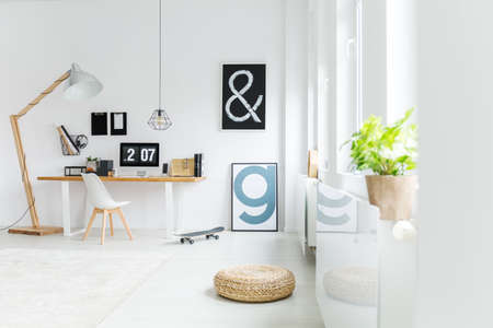Letter posters, wicker pouf and plants in scandinavian study workspace Stock Photo