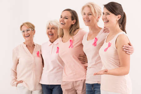 Women of all ages united with the pink ribbon of breast cancer awareness Stock Photo