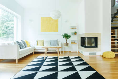 Black and white triangle carpet and yellow pouf on floor in open space interior with corner sofa and fireplace