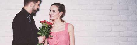 Hombre en camisa negra dando rosas a la atractiva mujer sonriente en vestido rosa de pie contra la pared de ladrillo blanco Foto de archivo - 87392509