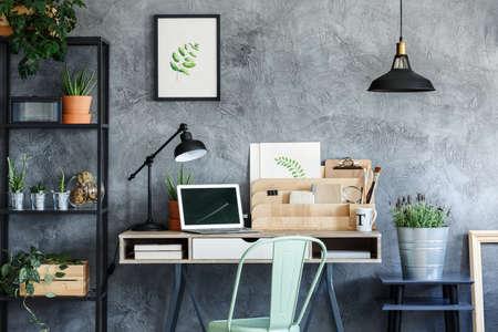 프리랜서의 방에 노트북과 책상 옆에 검은 의자에은 양동이에 라벤더 위에 검은 램프
