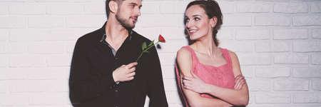 Hombre de camisa negra recogiendo sonriente mujer con vestido rosa, dándole una rosa roja Foto de archivo - 87244336