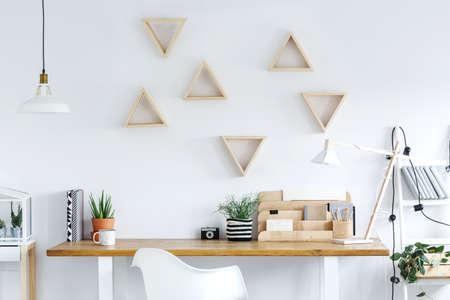 Houten bureau met kop koffiecamera en cactus in kleipot in helder huisbureau