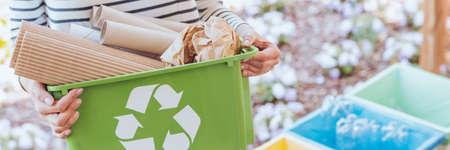 Pessoa ecológica que cuida do ecossistema, classificando papel para recipiente verde. Conceito de reciclagem