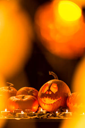 Carved Halloween lantern, pumpkins and candles on a dark background