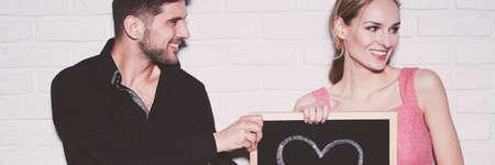 黒の t シャツの男は彼女に彼は黒板に描いた心を与えることによって女性に愛を告白します。 写真素材