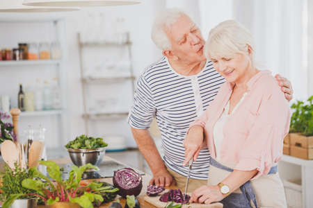 Older man is kissing wifes head while she is cutting cabbage on a vegetarian dinner