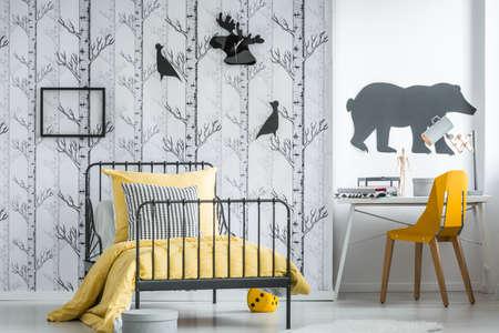 Modern studiegebied met gele stoel in de slaapkamer van de eenvoudige tiener met patroonhoofdkussen op bed