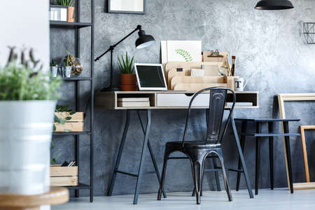 Black designed chair at desk with laptop in freelancers room with plants and wooden frames