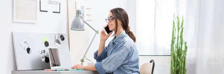 Lächelnde Geschäftsfrau, die auf Smartphone beim Sitzen am Schreibtisch mit Laptop im Innenministerium spricht Standard-Bild - 87588343