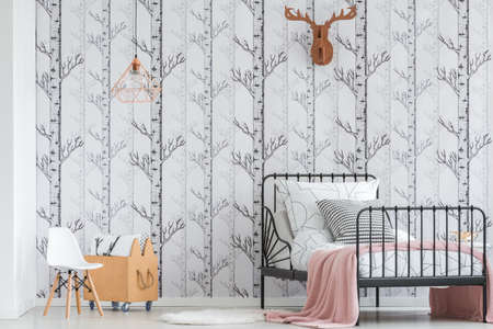 침대에 분홍색 담요와 어린이 침실에 베개와 나무 상자 옆에 흰색의 자 위의 구리 램프