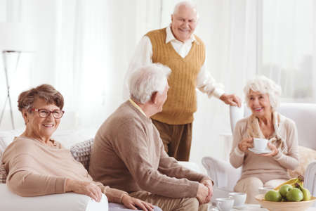 Two couples of elders spending time together in white room