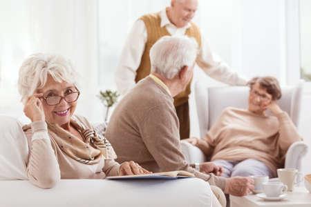 Smiling grandmother reads book in brown glasses during meeting Zdjęcie Seryjne - 87244378