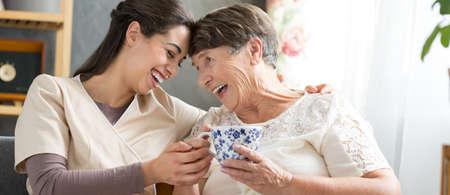 専門看護師と共通の部屋に座っていると、お茶を飲みながら笑っている笑顔のシニア女性
