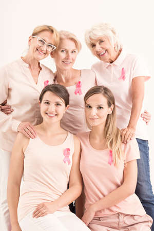 Women in pink shirts and pink ribbons are posing for a portrait picture. Breast cancer concept