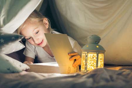 bedtime story: Happy girl reading book in creative indoor tent