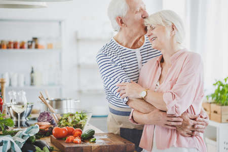 Grandpa hugs and kisses smiling grandma during cooking healthy meal in kitchen Stock Photo