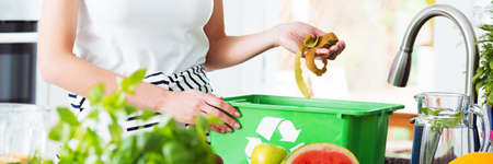 Aware woman throwing remains of fruit to green compost bin for biodegradable waste. Recycling concept