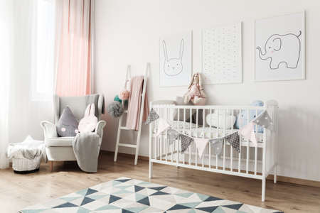 White baby's bed with banner and pillows against white wall with pictures in room with ladder and grey armchair Archivio Fotografico
