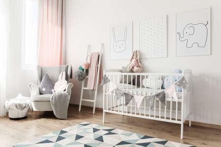 Het bed van de witte baby met banner en hoofdkussens tegen witte muur met beelden in ruimte met ladder en grijze leunstoel Stockfoto