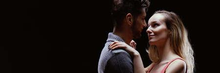 Feliz pareja bailando juntos contra el fondo negro, mirándose a los ojos Foto de archivo - 87392544
