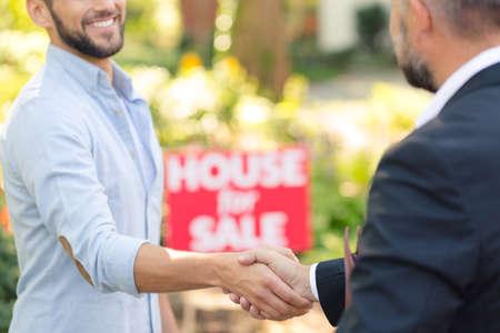 Close-up van professionele huisverkoper in pak schudden hand van de koper van een nieuw huis Stockfoto