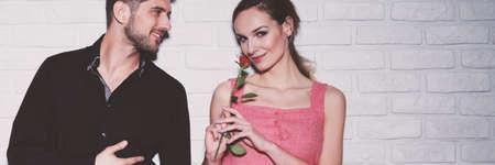 Linda mujer con vestido rosa sosteniendo una rosa roja que recibió de hombre guapo en camisa negra Foto de archivo - 87392548