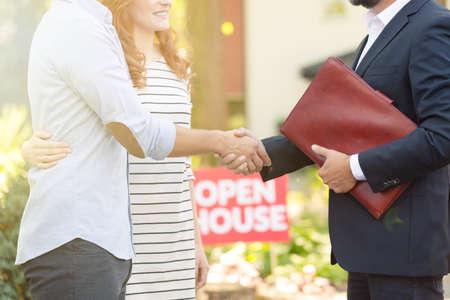Close-up van vastgoedadviseur feliciteren jonge klanten voor het kopen van een nieuw huis