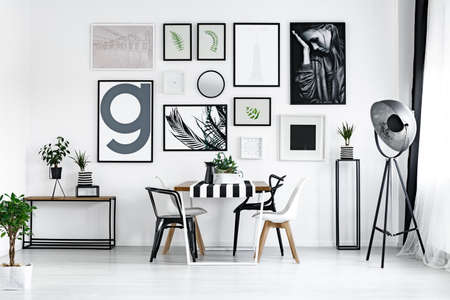 Room with plants and wooden table with modern white and black chairs