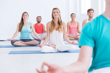 Happy people are meditating while sitting on mats on yoga classes Stock Photo