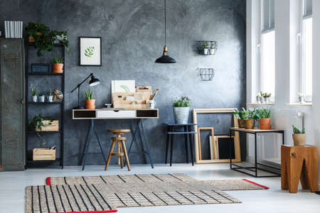 Plant in metal bucket on black stool in artistic home office with patterned carpet on white floor Reklamní fotografie
