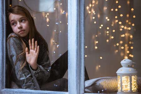 Triest kind kijkt uit het raam 's nachts