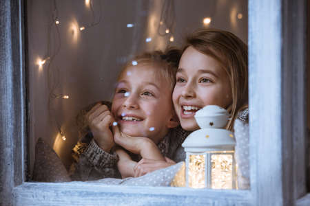 Happy, little girls standing beside window, at night