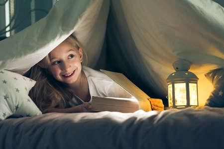 Happy girl lying with book in indoor tent Reklamní fotografie